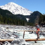 A hiker crosses the Nisqually on the bridge near Cougar Rock.