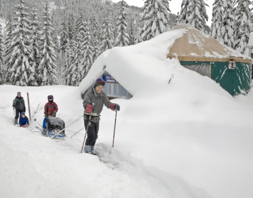 A happy family skis from the Mount Tahoma Trails yurt after a snow-filled adventure.