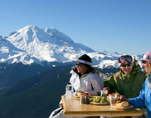 A group of people dining outdoors with a view of Mt Rainier