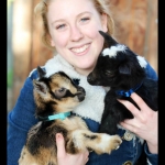 A woman holds two goat kids at Left Foot Farms