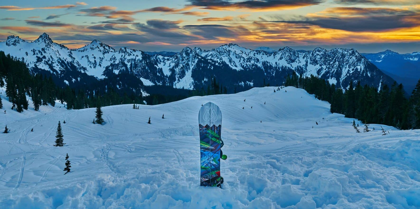 Backcountry sunset photo with snowboard in the snow by Rainier Mountain Sportz