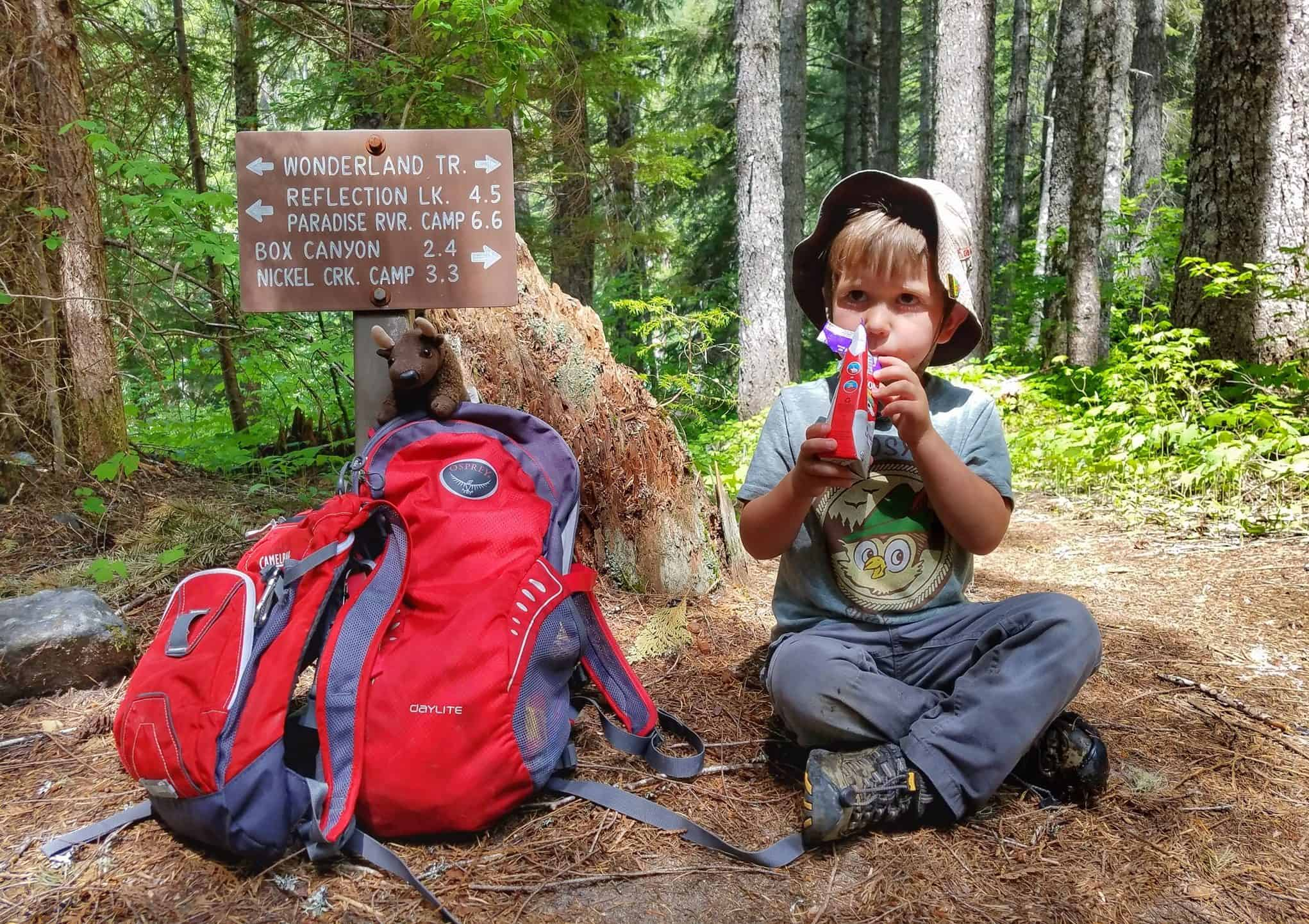 Young boy drinking from a carton while sitting by a trail sign