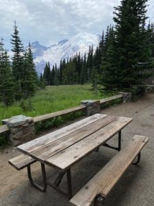 A picnic table at Sunrise, MRNP in the foreground with Mount Rainier in the background