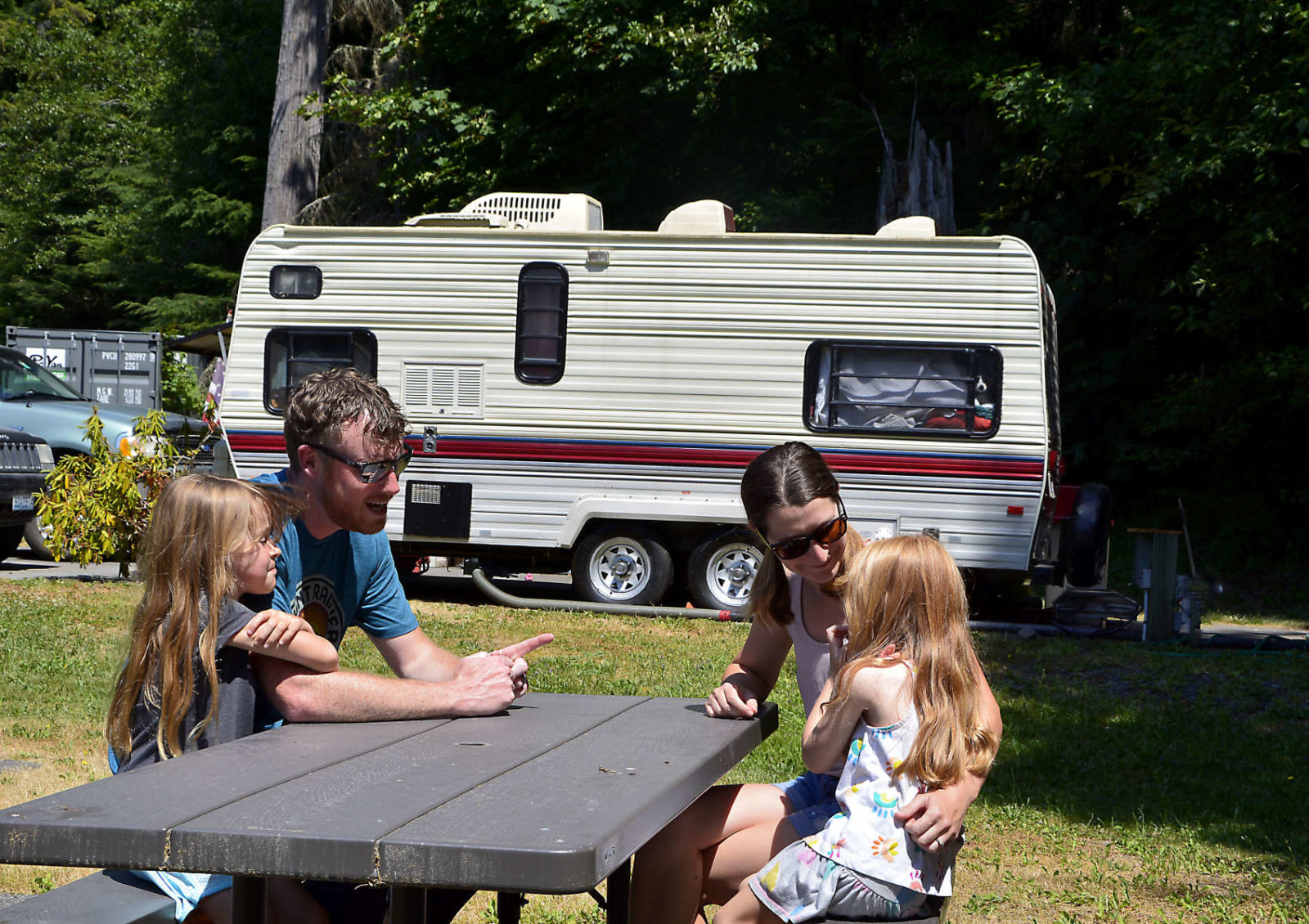 A family sits at a picnic table with an RV in the background