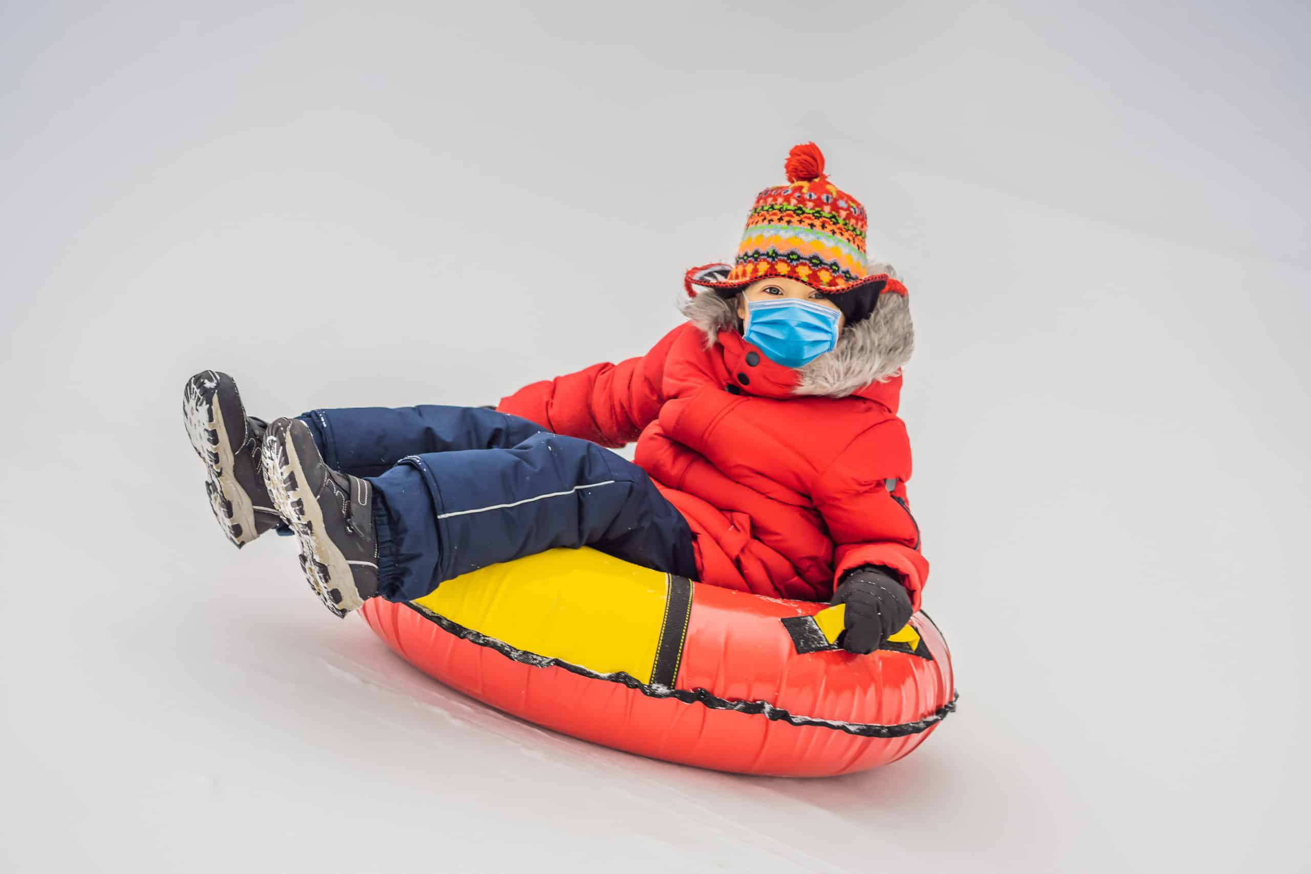 girl tubing on snow wearing a mask