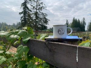 Coffee mug and book outside Red Cabin at Left Foot Farm