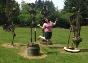 A woman poses by iron sculptures