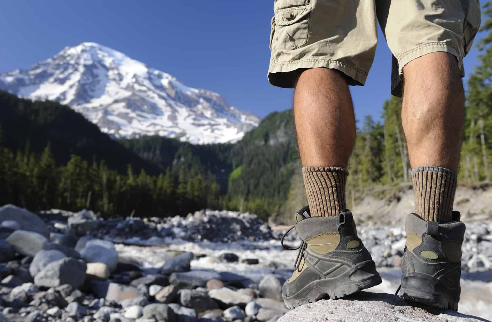 An iamge of a hiker standing by a river with Mount Rainier in the background