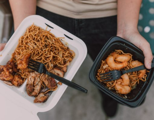 A person holds two take-out plates of Chinese food