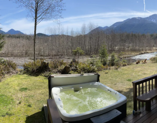 Outdoor hot tub with river view at The River House