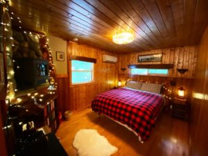 A queen size bed with air conditioning unit and gas fireplace